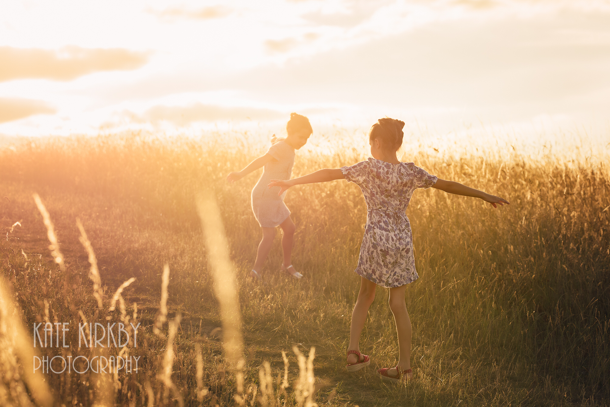 girls dancing in long grass at sunset