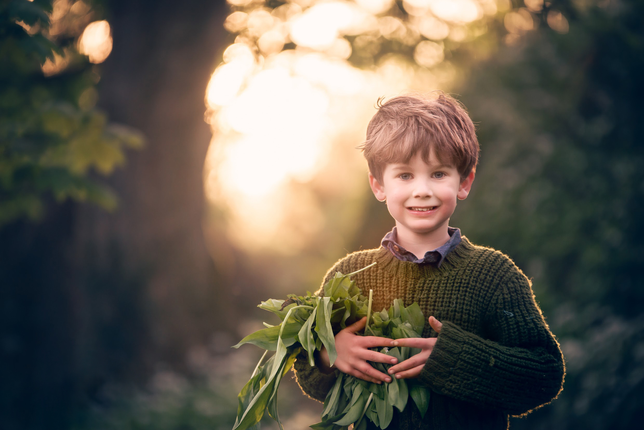 Boy smiling in the woods at sunset