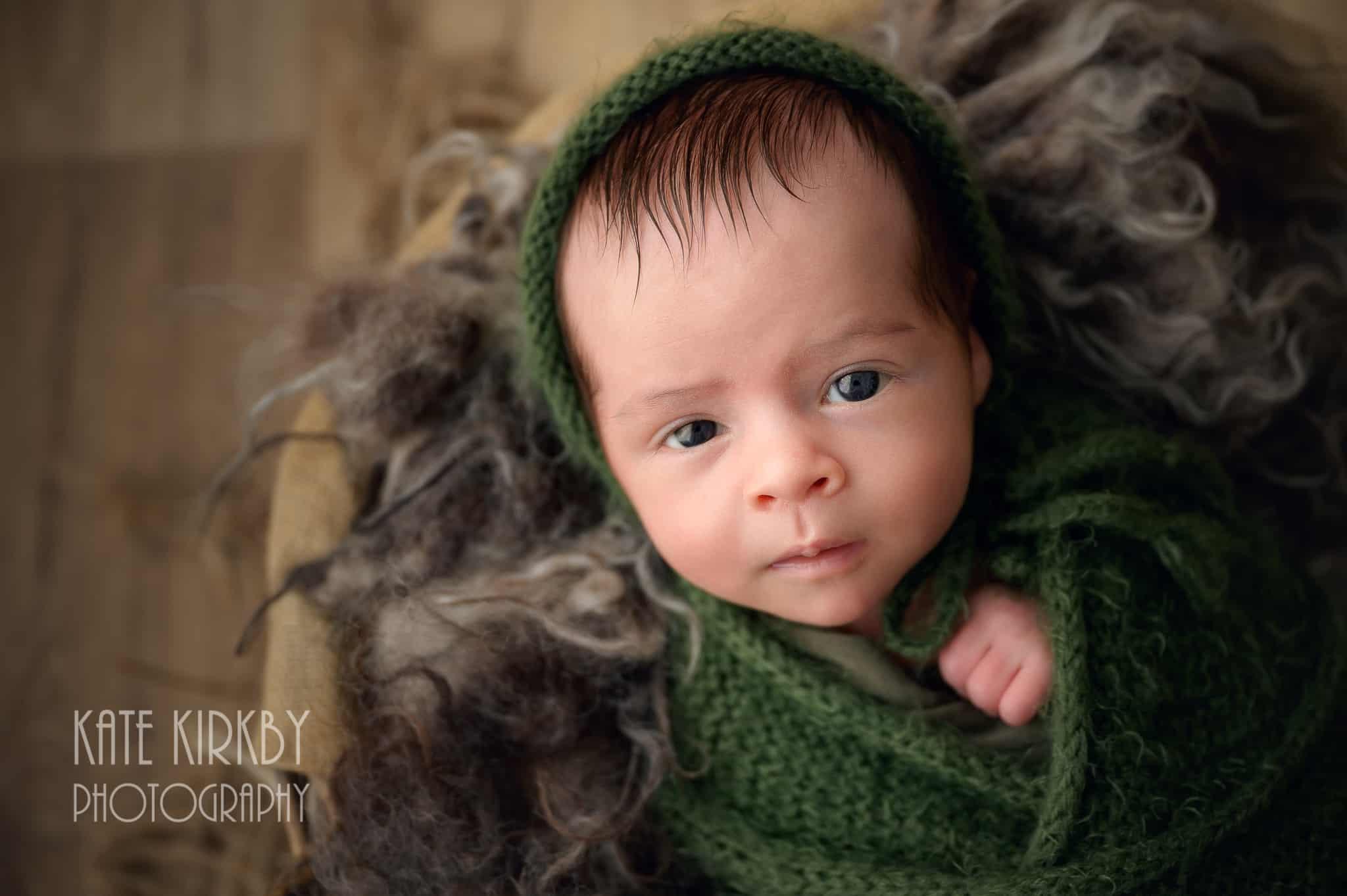 awake newborn wrap in green