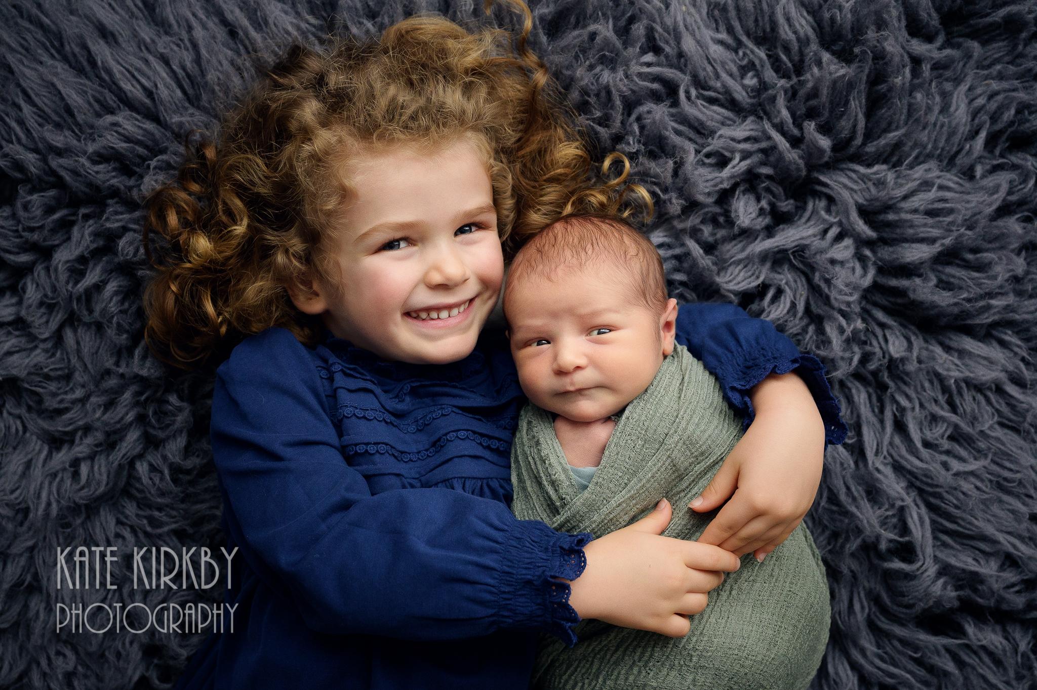 Big sister cuddling newborn on dark grey rug
